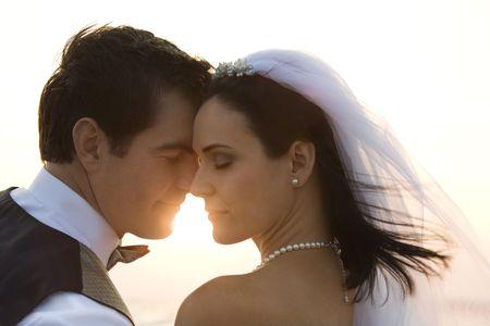 Imagen con iluminación posterior de un par de newlywed en la playa. Horizontal de disparo.