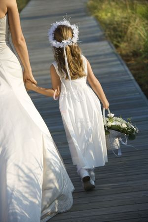 milestones: Cropped rear view of a bride walking and holding hands with a flower girl on the boardwalk. Vertical shot.
