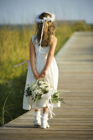 dress up: Rear view of a flower girl walking on a boardwalk holding a flower basket behind her back. Vertical shot.