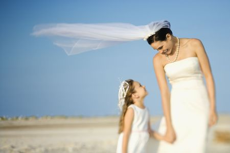 Bride and a flower girl look at each other on a sandy beach. Horizontal shot. photo