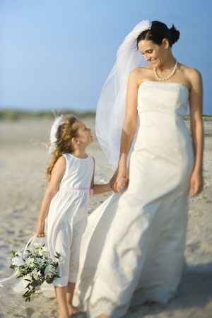 milestones: Bride and a flower girl hold hands on a sandy beach. Horizontal shot. Stock Photo