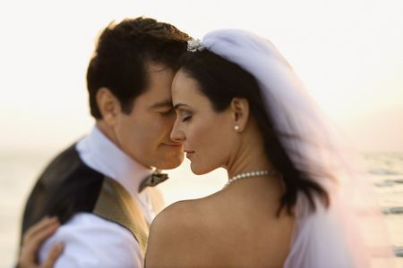 Newlyweds with their foreheads together affectionately on the beach. Horizontal shot. photo