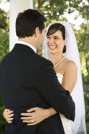 milestones: Smiling newlyweds hold each other outdoors. Vertical shot. Stock Photo