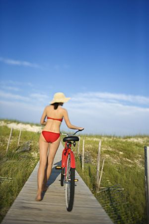 Rear view of a woman in a bikini walking her bicycle on the boardwalk. Vertical shot. photo
