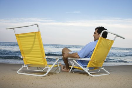 and the horizontal man: Man sits on the beach alone and looks at an empty chair. Horizontal shot.