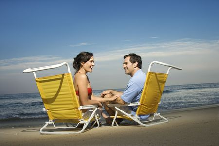 Man and woman sit in beach chairs and enjoy one another's company. Horizontal shot. Stock Photo - 6302453