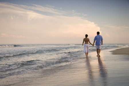 sandy beaches: Rear view of a couple walking on the beach, holding hands. Horizontal shot. Stock Photo