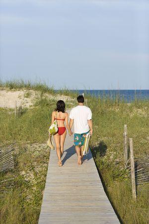 Rear view of a man and woman holding hands, walking down a beach boardwalk. Vertical shot. photo