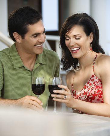 socializando: Par beber vino tinto en un caf� al aire libre. Un disparo vertical.  Foto de archivo