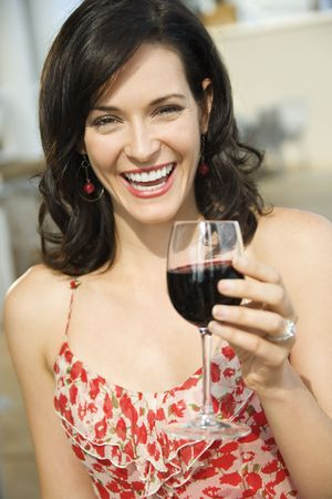 Woman toasts the camera with a glass of red wine. Vertical shot. Stock Photo - 6302400