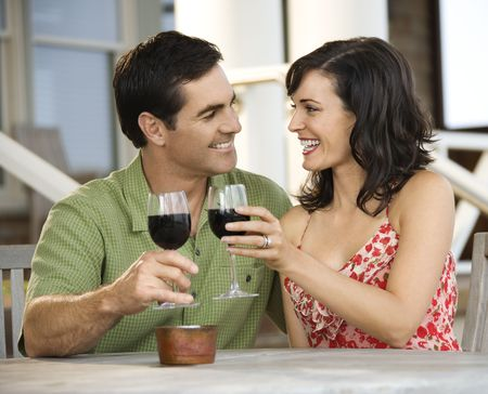 Man and woman toast with red wine glasses at an outdoor cafe. Horizontal shot. photo