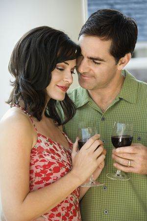 Man and woman act affectionately while holding red wine. Vertical shot. photo