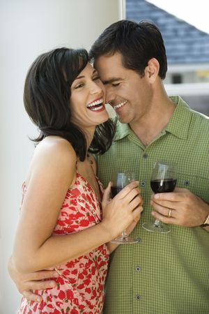 husbands: Man and woman laugh while standing with glasses of wine. Vertical shot.
