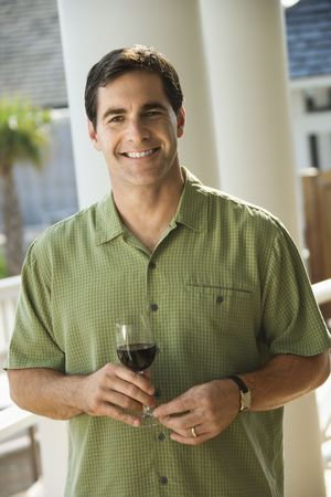 Portrait of smiling man standing outside with glass of red wine. Vertical shot. photo