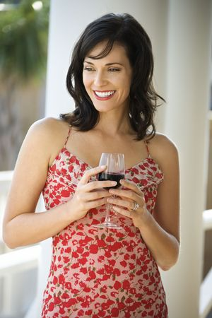 30s adult: Portrait of happy woman standing and holding a glass of red wine. Vertical shot. Stock Photo