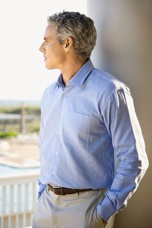 man profile: Portrait of a man standing on porch with his back to a column looking out towards the coast. Stock Photo