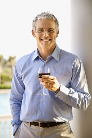 only mid adult men: Portrait of a middle aged man on a terrace drinking red wine. Vertical shot.