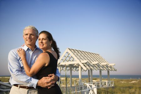 Attractive couple embrace on the beach with arbor in background. Horizontal shot. photo