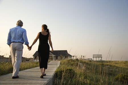 looking away from camera: Couple walk hand in hand on a boardwalk towards a beach pavilion. Horizontal shot. Stock Photo