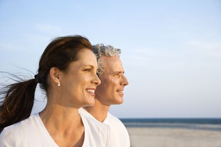 midlife: Side view of smiling middle aged couple on beach looking off into the distance together. Horizontal shot.