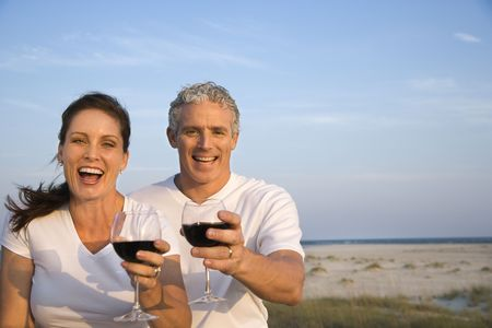 midlife: Happy couple drink wine on the beach and raise their glasses to the camera. Horizontal shot. Stock Photo