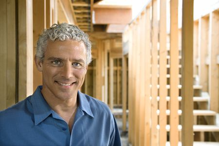 Man stands inside a partially constructed home and smiles towards the camera. Horizontal shot. Stock Photo - 6302641