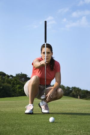 crouching: Woman crouches and lines up her putt on a golf course. Vertical shot. Stock Photo
