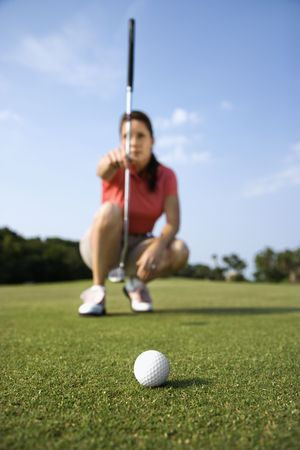 Closeup of a golf-ball with a woman lining up her putt in the background. Vertical shot. photo