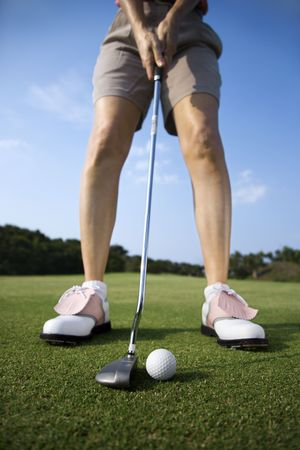 Closeup of a woman golfer about to putt on a golf green. Vertical shot. photo
