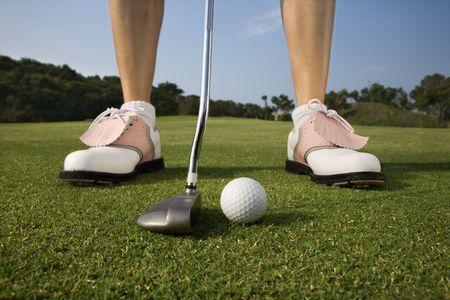 Closeup of a woman golfer about to make a putt. Horizontal shot. photo
