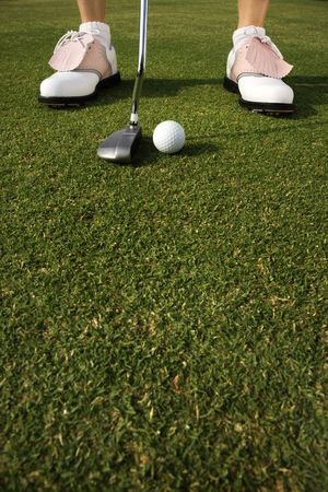 Closeup of a golf ball and the shoes of a golfer about to putt. Vertical shot. photo