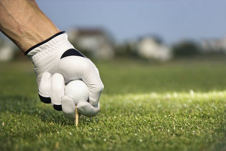 Male golfer places a golf ball and tee in the ground. Horizontal shot. photo