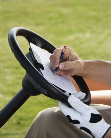 golf cart: Male golfer writing his golf score while sitting in a golf cart. Vertical shot.