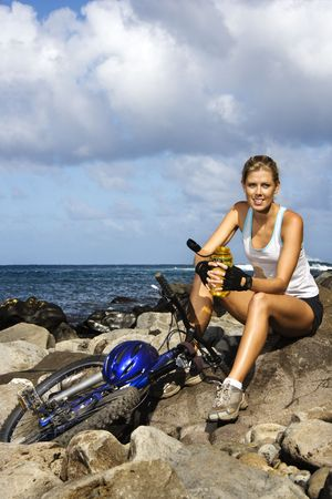Attractive young woman holding a water bottle and sitting next to a bicycle on a rocky beach.  She is smiling at the camera. Vertical shot.