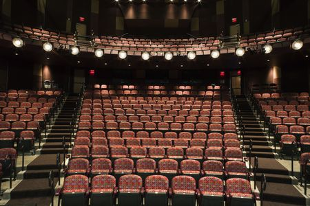 balcony: Rows of empty seats in theater seen from stage. Horizontal shot.