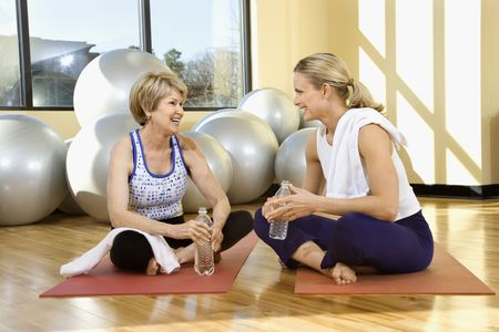 Two women enjoy a conversation while sitting on a gym floor. They are on exercise mats and balance balls are in the background. Horizontal shot. photo