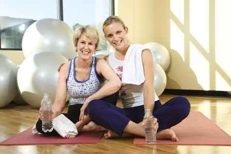 Two women smile towards the camera while sitting on the floor of a gym. One woman has her arm around the other and balance balls can be seen in the background. Horizontal shot. photo