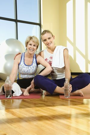 Two women smile towards the camera at the gym. They are sitting on the floor in front of a window. Vertical shot. photo