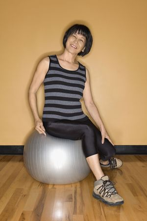 Asian woman smiles towards the camera as she sits on a balance ball in the gym. Vertical shot. photo