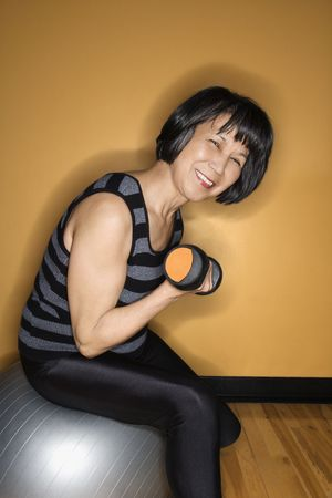 Asian woman sits on a balance ball while lifting a hand weight. She is smiling towards the camera. Vertical shot. photo