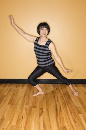 Asian woman stands with outstretched arms while performing a yoga position at the gym. Vertical shot. photo