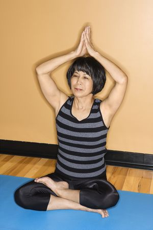 Asian woman sits on an exercise mat at the gym and has her arms raised in a yoga position. Vertical shot. photo