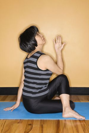 holistic view: Asian woman practices yoga on an exercise mat at the gym. Vertical shot.