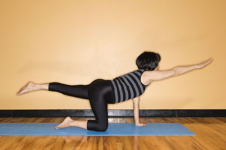 holistic view: Woman at the gym practices yoga with one outstretched arm and leg. Horizontal shot. Stock Photo