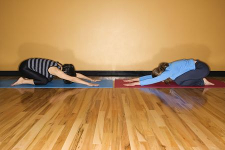 Two women kneel towards each other in childs pose yoga position at the gym. Horizontal shot. photo