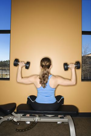 woman lifting weights: Rear view of a woman sitting on a weightlifting bench, lifting dumbbells. Vertical shot.