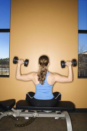 Vista posterior de una mujer sentada en un banco de levantamiento de pesas, levantamiento de pesas. Un disparo vertical.  Foto de archivo - 6395639