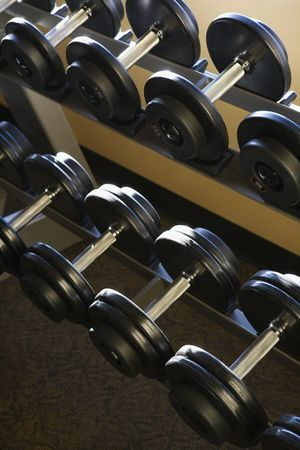 Two rows of dumbbells on a weight rack. Vertical shot. Stock Photo