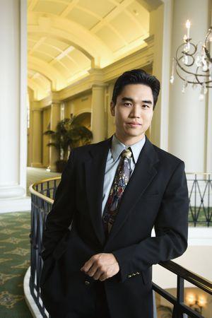 Porträt des eine asiatische Geschäftsmann, die auf einer Schiene in einem gehobenen Hotel lehnte. Vertikale erschossen.