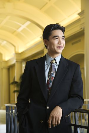 Portrait of an Asian businessman leaning on a rail in an upscale hotel. Vertical shot. Stock Photo - 6455254